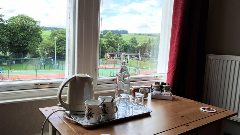 Bedroom with either twin beds or king size bed, consists of en-suite shower room, chairs over looking the tennis courts and Moffat Hills, there is a desk and chair available, tea and coffee making facilities, flat screen TV and WiFi.