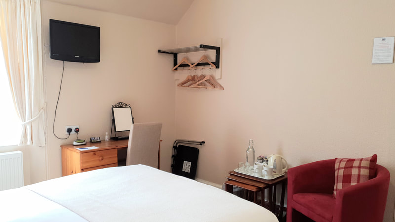 Double room consisting of a double bed, an en-suite shower room, flat screen TV with tea and coffee making facilities, there is a desk and chair, a clothes rail to hang coats and clothes. The room over looks the garden.