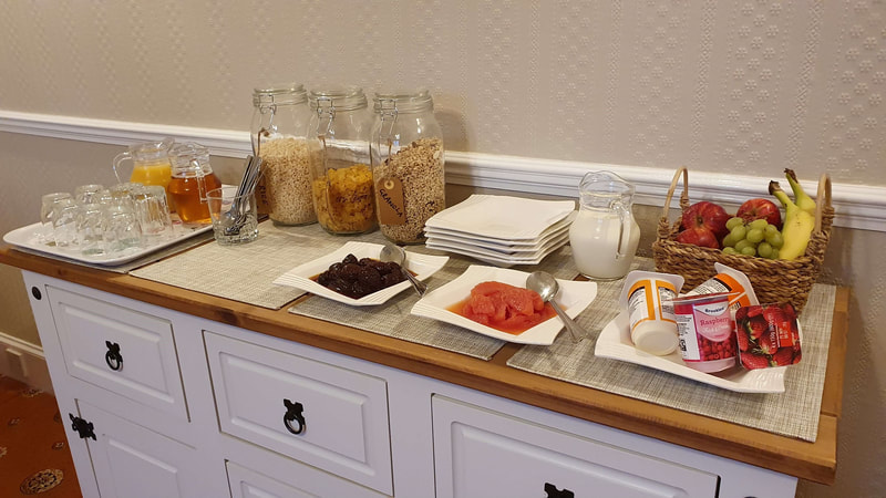 Buffet table with cereal, fresh fruit, prunes, grapefruit, milk, yogurts and fruit juice