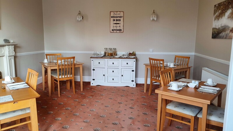 Dining Room with tables that have condiments and cutlery on them with chairs, buffet table with a variety of cereals, fruit, yogurts, prunes, grapefruit and milk.